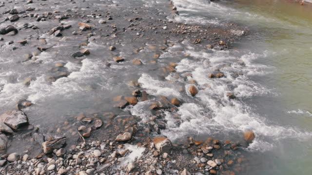 vídeos de stock, filmes e b-roll de voando sobre o rio wild mountain fluindo com pedras de pedra e corredeiras - penedo