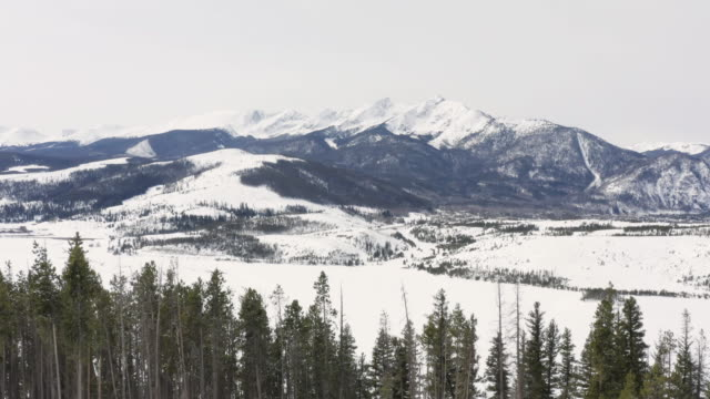 Flying Over Winter Trees Reveal Snowy Rocky Mountain Valley Near Breckenridge Colorado