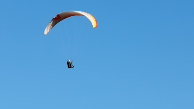 flying paraglider on a background of the sun and beautiful clouds.summer day - парапланеризм стоковые видео и кадры b-roll