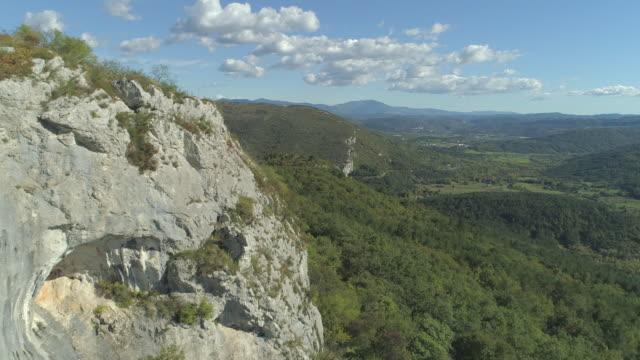 vídeos de stock, filmes e b-roll de aérea: voando por falésia rochosa em direção a prados e colinas, cobertas por floresta. - eslovênia