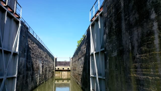 Flying through ship lock on side of hydroelectric powerplant, spring day