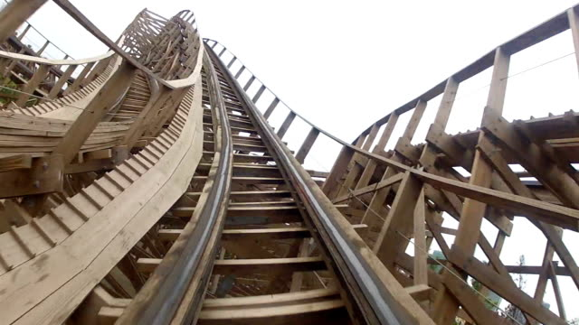 flying through turns on wooden roller coaster - luna park video stock e b–roll