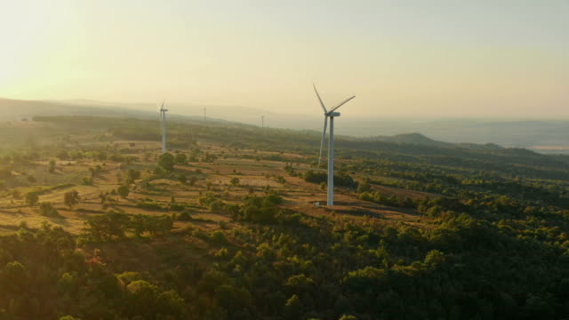 Flying to the Wind turbines generating renewable and sustainable energy in the mountains.