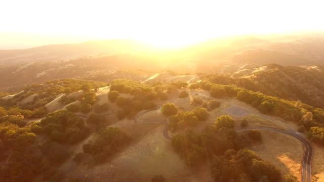 fliegen in richtung brillanten sonnenuntergang am goldenen horizont - anhöhe stock-videos und b-roll-filmmaterial