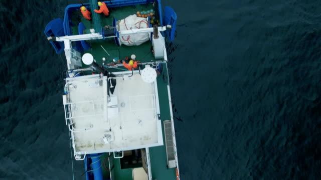 vídeos de stock, filmes e b-roll de voando em direção um navio de pesca comercial que arrasto puxa - países bálticos