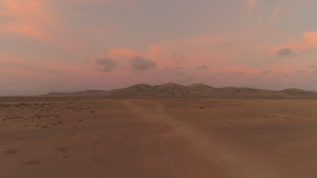 AERIAL: Flying towards large volcanic structure in pink colored desert sunset. video