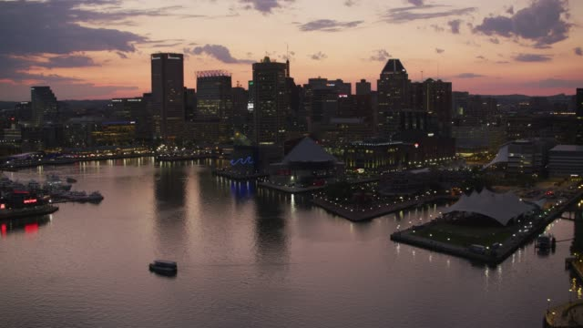 Flying up inner harbor to downtown Baltimore at sunset. video