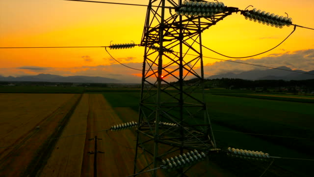 AERIAL: Flying up the high voltage electricity tower at sunset AERIAL: Flying up the high voltage electricity tower and power lines at sunset above the beautiful agricultural field high voltage sign stock videos & royalty-free footage