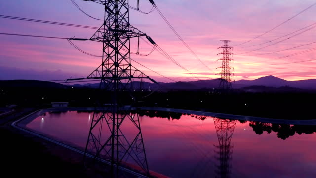 AERIAL: Flying up the high voltage electricity tower at sunset AERIAL: Flying up the high voltage electricity tower at sunset in Asia power supply stock videos & royalty-free footage