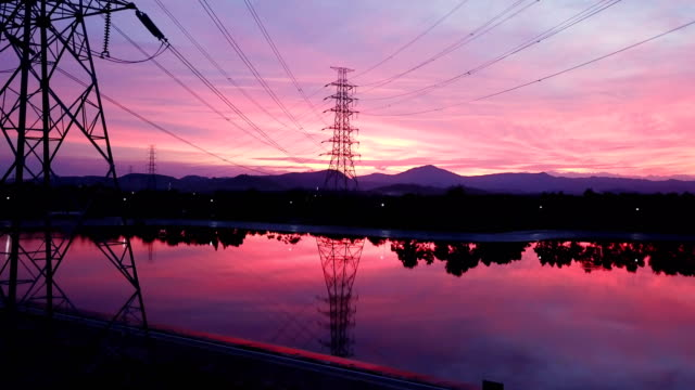 aerial: flying up the high voltage electricity tower at sunset - cavo dell'alta tensione video stock e b–roll