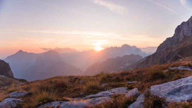 vídeos y material grabado en eventos de stock de vuelo, moviéndose hacia el borde de la montaña, admirando la vista de las montañas circundantes y el cielo colorido iluminado por la luz de la puesta de sol - terreno extremo