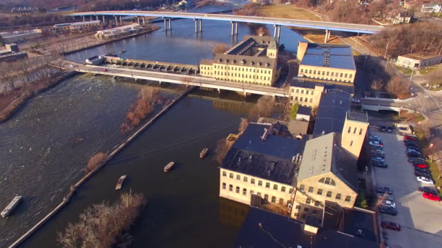 Flyover of springtime riverfront with buildings, damn, bridge, raging waters video