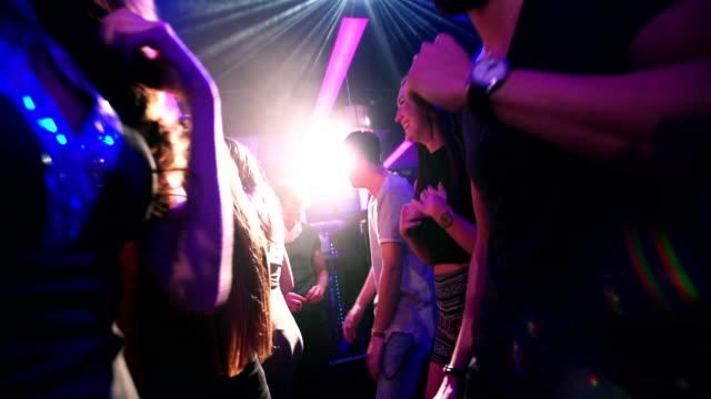 Flythrough shot of energetic party people dancing in club