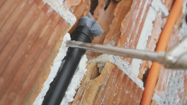 pu foam being sprayed around the black pipe in the wall - poliuretano polimero video stock e b–roll