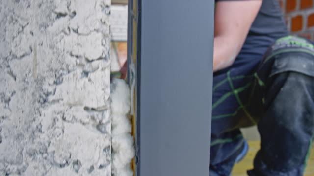 pu foam being used to install a door frame - poliuretano polimero video stock e b–roll
