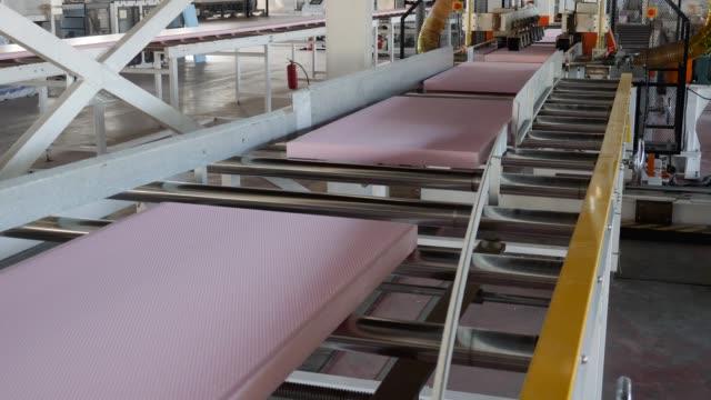 foam plastic on assembly belt line, automatic equipment for production of foam polystyrene - poliuretano polimero video stock e b–roll