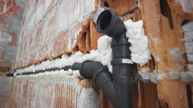 ds pu foam surrounding a plastic pipe in the wall opening - poliuretano polimero video stock e b–roll