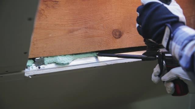 isolamento della finestra in schiuma sulla costruzione in legno. costruire un'eco-casa. isolamento termico - gommapiuma video stock e b–roll