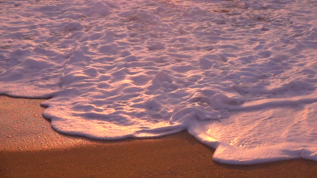 CLOSE UP: Foaming water sweeps over the sandy beach on a beautiful evening.