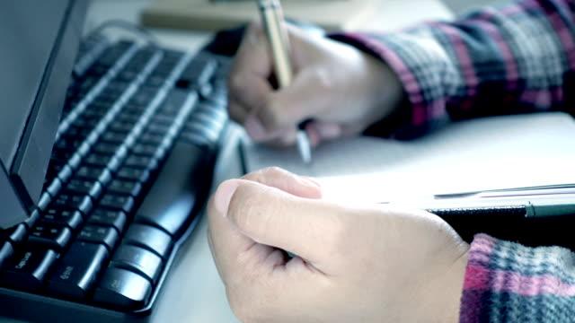 fokus för kvinna hand med suddig av ta anteckningar på skrivbord - linjerat papper bakgrund bildbanksvideor och videomaterial från bakom kulisserna
