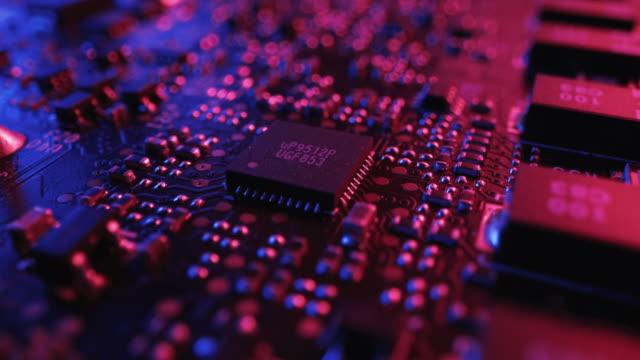 vídeos y material grabado en eventos de stock de concéntrese en un microchip, procesador de cpu. placa de circuito impreso / placa base de ordenador con componentes: dentro del dispositivo electrónico. colores de neón. concepto de seguridad cibernética. disparo macro giratorio - placa madre