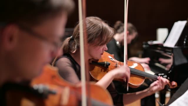 Focus on a young woman playing the violin with a string quartet and grand piano