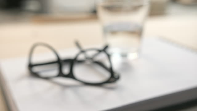 Focus on eyeglasses Eyeglasses, sketch pad and glass of water coming tin to focus image focus technique stock videos & royalty-free footage