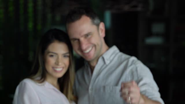 vordergrund des glücklichen paares neuen besitzer eines hauses nach vorne halten ihre schlüssel und lächelt in die kamera im fokus - hausschlüssel stock-videos und b-roll-filmmaterial