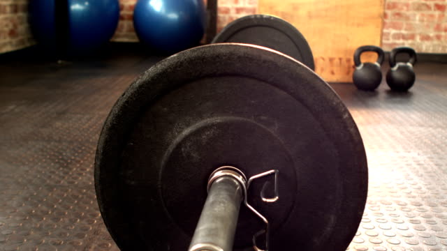 Focus on heavy barbell in gym gym video