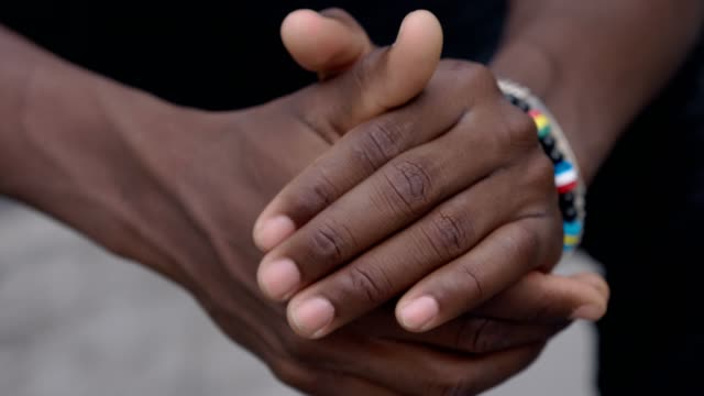 vidéos et rushes de se concentrer sur des problèmes, des soucis, des pensées. jeune homme noir seul se frotter les mains pensant - peau humaine