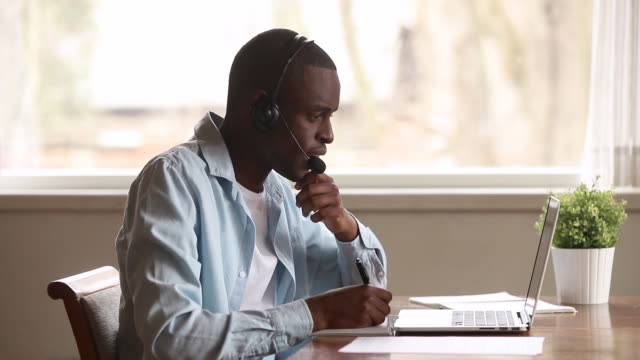 Focused african businessman wear headset look at laptop make notes