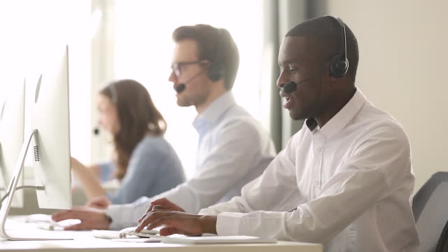 vídeos de stock e filmes b-roll de focused african call center agent wear wireless headset consulting customer - apoio