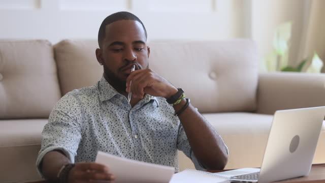 uomo d'affari di etnia africana focalizzato che lavora da remoto sul computer. - curiosità video stock e b–roll