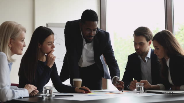 Focused african male manager mentor and multiethnic team analyze paperwork Focused african male manager executive mentor and multiethnic team analyze paperwork discuss project plan share ideas brainstorm work together in teamwork at table office group corporate meeting ceo stock videos & royalty-free footage