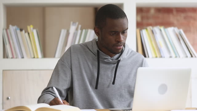Focused african student study online on computer make notes
