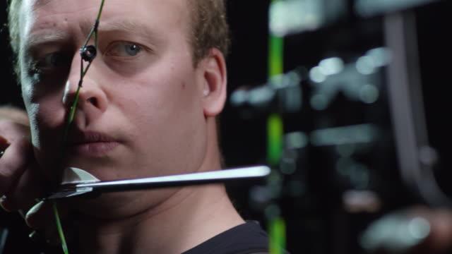 vidéos et rushes de ciblée archer lançant la flèche sur fond noir - tir à l'arc
