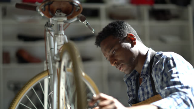Focused black man repairing a bicycle on a table and using a tool