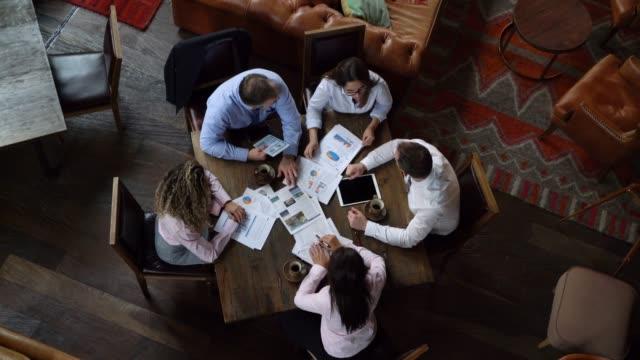 vídeos y material grabado en eventos de stock de grupo empresarial enfocado en una reunión hablando mirando algunos documentos y tablet - zoom meeting