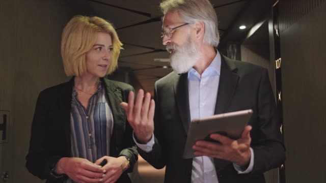 vídeos de stock e filmes b-roll de focused businesspeople using digital tablet in hotel hallway - senior business woman tablet