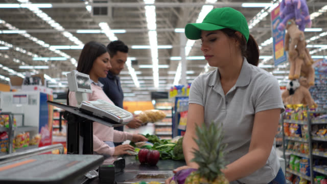 vídeos de stock e filmes b-roll de focused cashier registering products at checkout in a megastore for young couple - supermarket worker