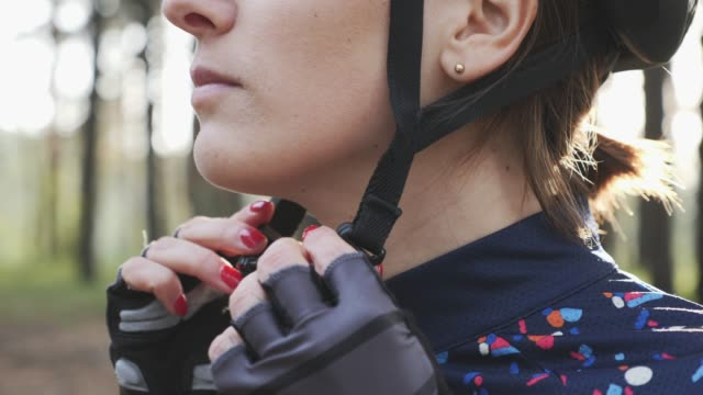 focused cycling woman puts on helmet and clips harness before the triathlon race. triathlon concept. slow motion - pantaloncini video stock e b–roll