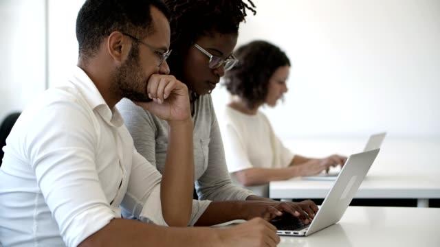 vídeos de stock, filmes e b-roll de empregados focados que usam o portátil ao sentar-se no escritório - rh