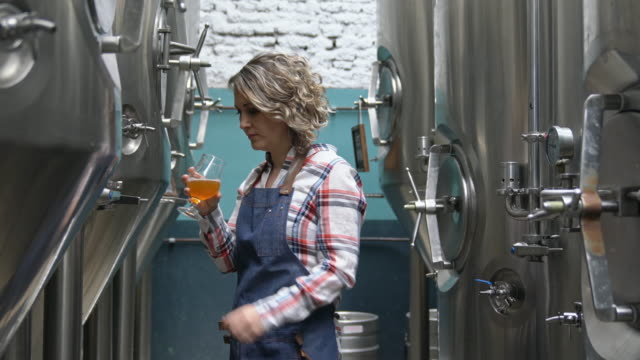 Focused Female Brewery Worker Checking Sample for Clarity