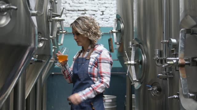 明確さのために焦点を当てた女性醸造労働者チェックサンプル - 醸造所点の映像素材/bロール