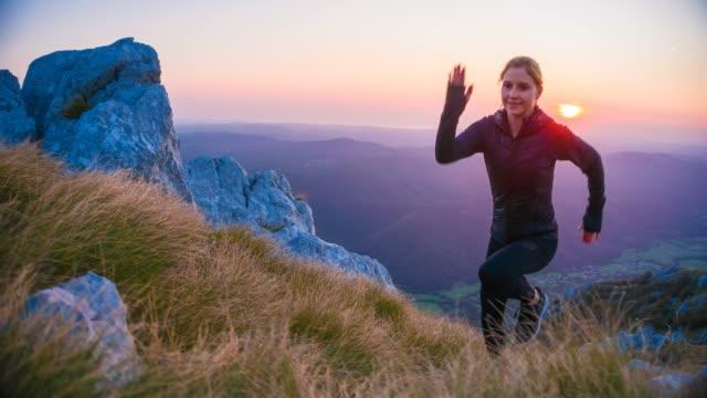 fokuserade kvinnliga löpare kör till toppen av berget - jogging hill bildbanksvideor och videomaterial från bakom kulisserna
