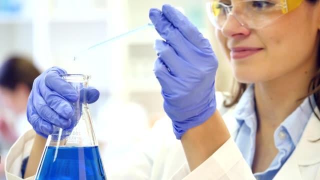 Focada feminina cientista gotas líquido num copo de precipitação - vídeo