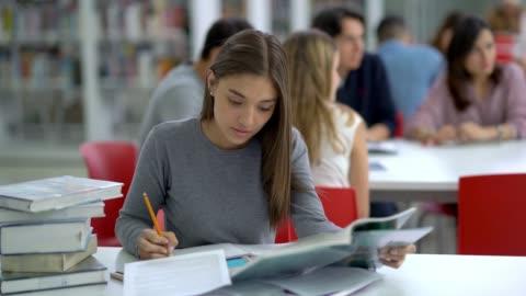 vídeos y material grabado en eventos de stock de mujer joven estudiante en la biblioteca leyendo libros y tomando notas de centrado - estudiante