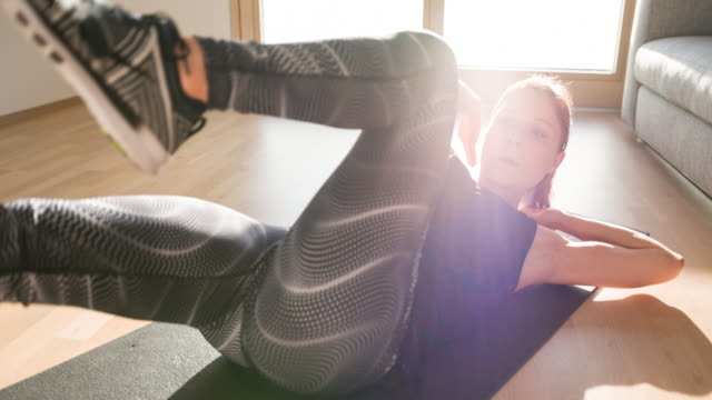vídeos de stock e filmes b-roll de focused fit woman doing bicycle crunches on exercise mat at home - treino em casa