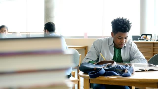 vidéos et rushes de axé sur les études étudiant lycée masculin pour test dans la bibliothèque de l'école - élève