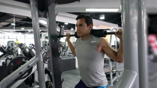 vídeos de stock e filmes b-roll de focused man at the gym working out legs and back with weights at the gym - aparelho de musculação